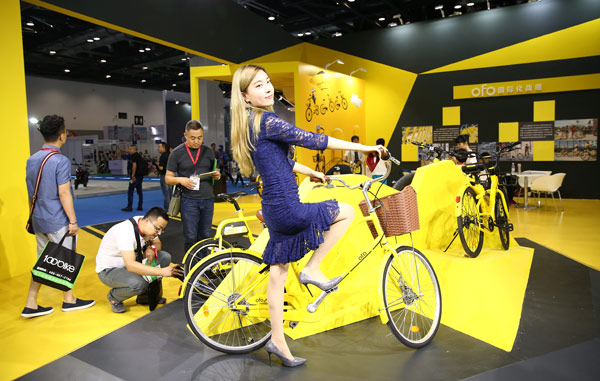 A woman tries out an Ofo bike at an industry expo in Beijing. Image: Zou Hong/China Daily