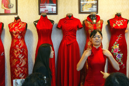 customer tries on a traditional Chinese Qipao in a garment shop in