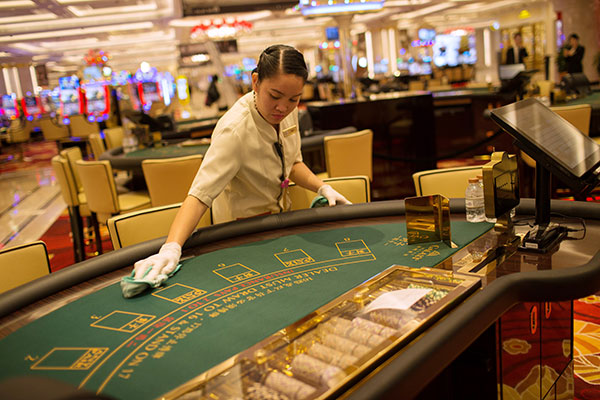 an employee cleans blackjack table inside the galaxy macao
