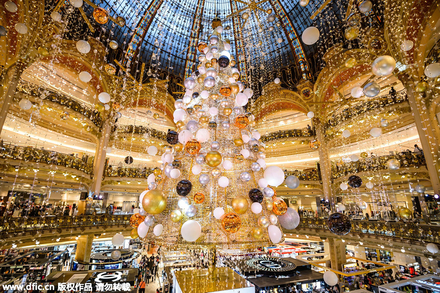 A Christmas tree stands under the dome of the Galeries Lafayette department  store in Paris, France, Nov 6, 2015. As Christmas comes, sellers decorated  their ... - Christmas Lights Across The World's Shopping Districts[5