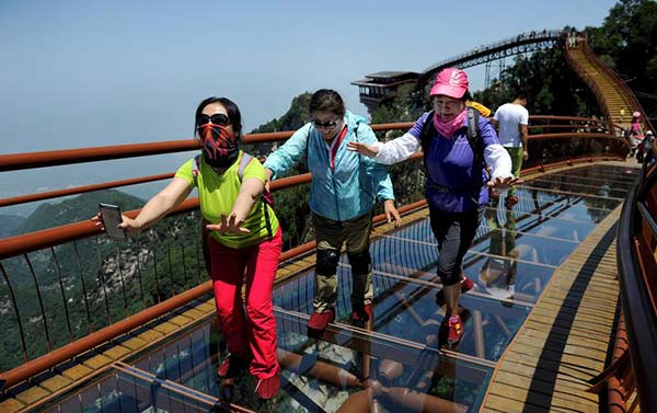 Tourists stretch to walk on a 69 meter long glass pathway built along