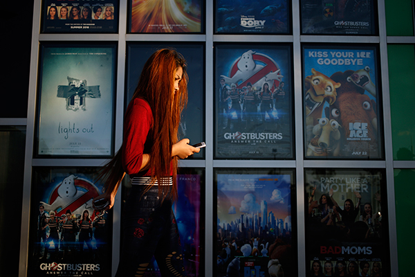 A Woman Walks Past Display Of Movie Posters Outside An AMC Entertainment Inc Theater In West Chester Ohio Photo Agencies