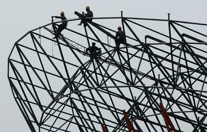 Workers perch on a steel structure at the construction site for a giant roof in Xiangfan, central China's Hubei province April 24, 2006.