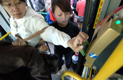 a bus rider uses his smart card to高清图片