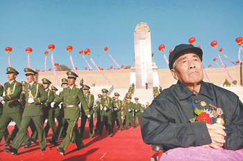 Veteran Red Army soldier Li Zhanrong, 86, sits in front of the Long March Monument at Jiangtaibao of Xiji County in Northwest China's Ningxia Hui Autonomous Region yesterday. The Long March ended at Jiangtaibao on October 22, 1936, after which the Red Army headed to Yan'an where the new CPC headquarters was established. (Xinhua)