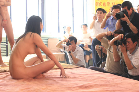 Professional and amateur photographers shoot pictures of nude models at an ...