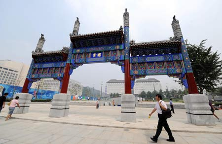 People walk past the Xidan Pailou, a decorated archway, at the new Xidan Cultural Square in Beijing, capital of China