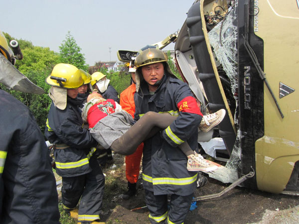 Fire fighters carry an injured passenger after a collision between a truck and bus killed 13 people and left many injured in the Changshu section on an expressway in E China's Jiangsu Province, April 22, 2012.