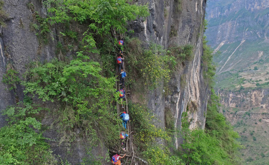 Kids climb vine ladder in 'cliff village' in Sichuan