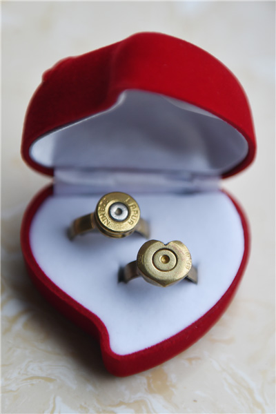 Couples exchange bullet shell rings at group wedding in military