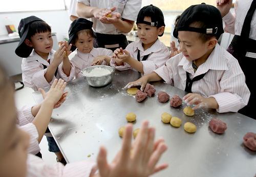市商业局幼儿园的小朋友在面点师的指导下学做月饼