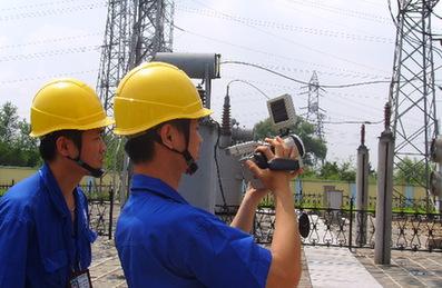 抚顺供电公司的工作人员用红外线仪器测试设备节点的温度