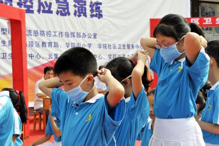 2009年7月6日 湖北宜昌举行暑期甲型h1n1流感防控应急演练 7月6日,宜昌市学院街小学的学生在演练中戴口罩.
