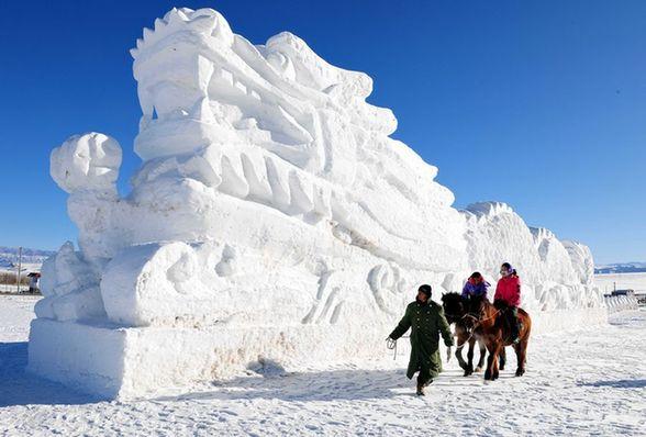 1月2日,游客在新疆哈密松树塘滑雪场冰雪雕塑园内骑马观赏雪塑作品