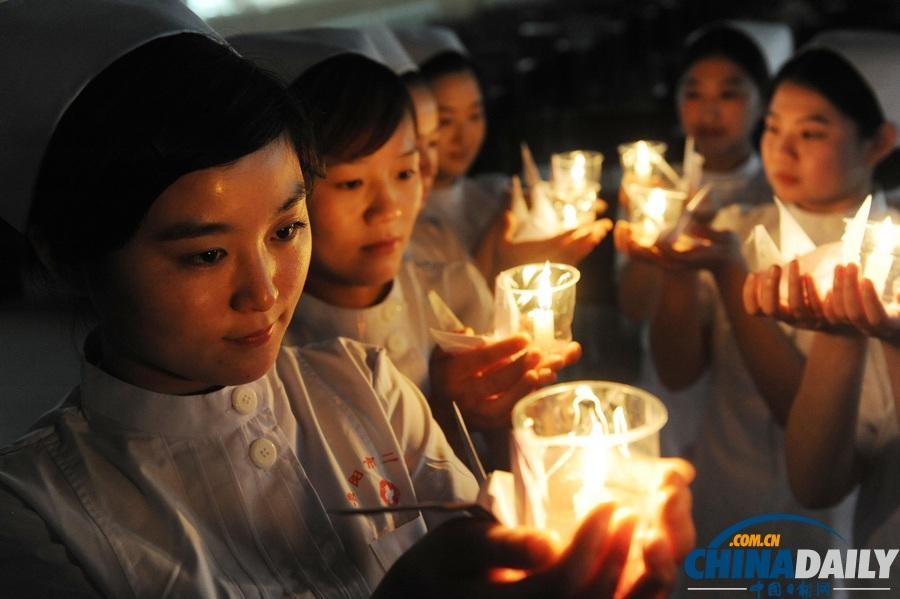 4月23日,安徽省阜阳市第二人民医院的护士手捧蜡烛和千纸鹤为地震灾区