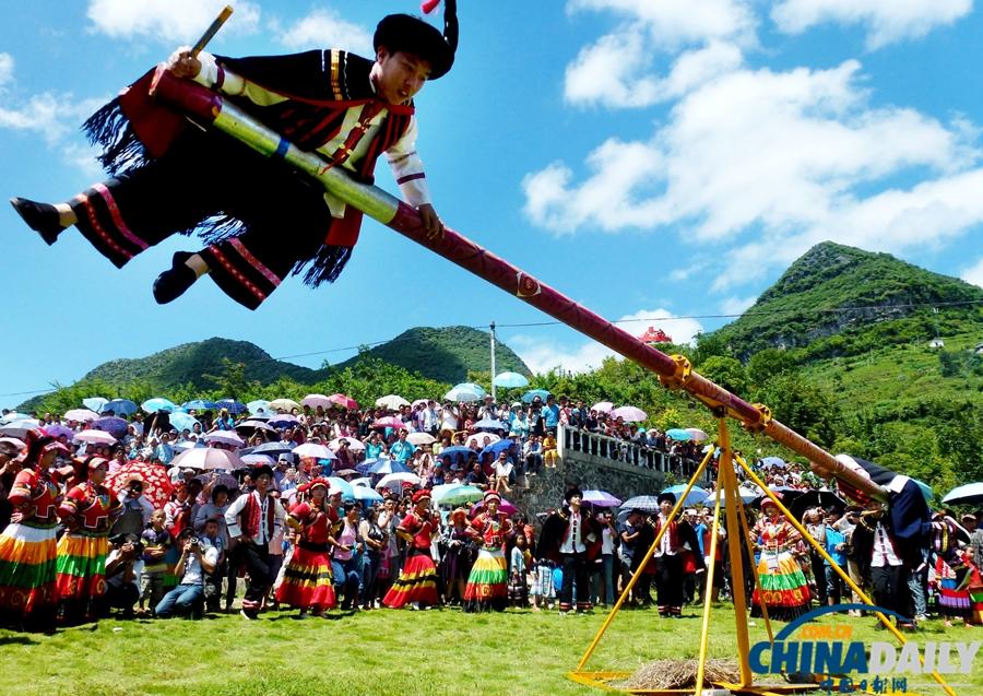 2013年7月31日,广西壮族自治区百色市隆林县举行2013年彝族火把节,彝族小伙子在给四方宾朋表演彝族打磨秋。火把节是彝族群众的传统节日,流行于广西、云南、贵州和四川等彝族地区。 (罗郅肯 摄)