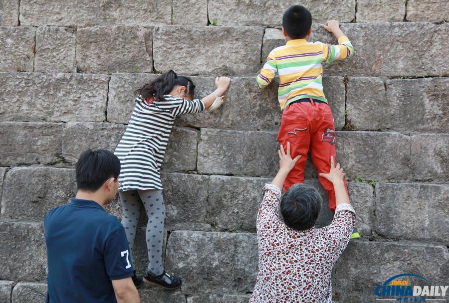 南京/江苏省南京市,几个小朋友在家长的托举下,在攀爬已有六百多年...