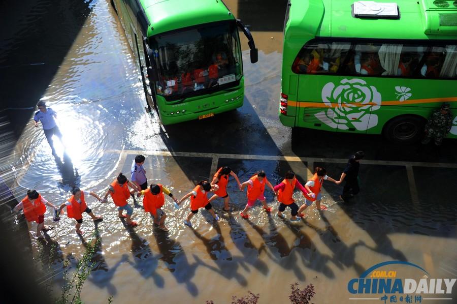 摄影 陈斌荣/在押人员排队在洪水中转移。(陈斌荣摄)