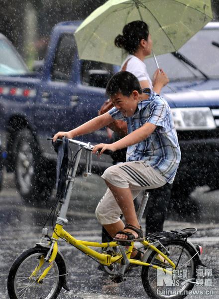 7月14日,一个男孩儿在雨中骑车.