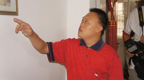 吴春忠的儿子凝视着照片上的父亲-心系民众的好警察 百姓心中的好所