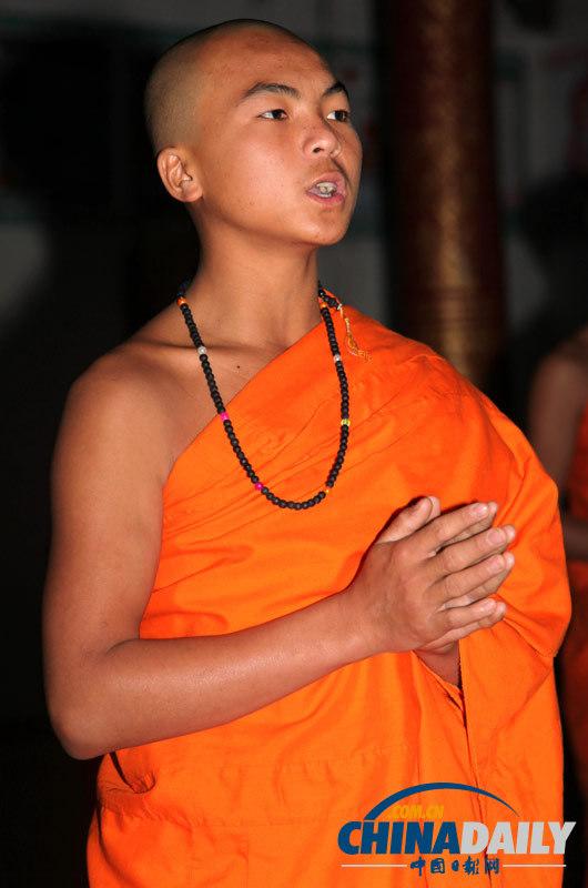 在西双版纳曼冷村佛寺,一位小和尚在还俗仪式前诵经念佛.