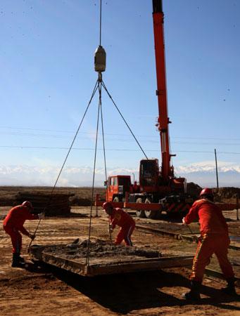 10月15日,西部钻探克拉玛依钻井公司安装工人正在铺设新井场钢木基础.图片