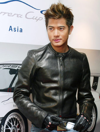 Hong Kong Singer Actor Aaron Kwok Poses In Front Of A Poster For