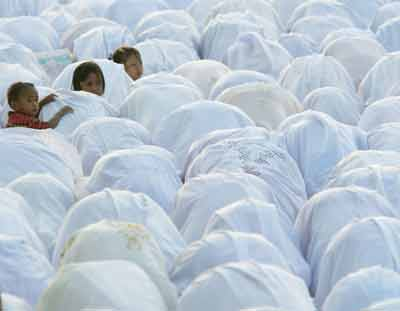 Muslim women pray during the Muslim holiday of Eid al- Adha or day of sacrifice at the grand mosque in the tsunami-hit city of Banda Aceh, on the Indonesian island of Sumatra January 21, 2005. Survivors in tsunami-hit Aceh crowded battered mosques to pray during an Islamic festival on Friday as aid workers found many toddlers in Indonesia were likely among the 225,000 killed by the Indian Ocean wave. [Reuters]