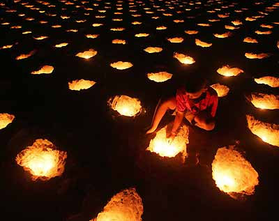 A young Thai lights candles during a vigil for tsunami victims on Patong beach in Thailand's tropical island of Phuket January 31, 2005. The Dec. 26 tsunami killed more than 5,300 people in Thailand and devastated several dozen luxury hotels at popular resorts in Phuket, Krabi and Khao Lak along its southwest coast. [Reuters]