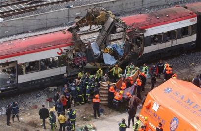 Rescue workers cover up bodies by a bomb damaged passenger train following a number of explosions on trains in Madrid, Spain, in this March 11, 2004 file photo. [AP/file]