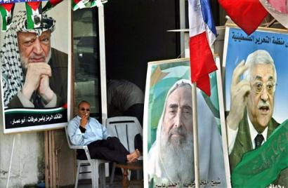 A Palestinian man sits in front of a store decorated with pictures of late Palestinian leader Yasser Arafat, left, late Hamas spiritual leader Sheik Ahmed Yassin, centre, and Palestinian Authority President Mahmoud Abbas, also known as Abu Mazen, right, in Gaza city, Thursday April 14, 2005. The Palestinian militant group Hamas on Thursday accused the ruling Fatah movement of trying to delay an upcoming parliamentary election, and said it was lobbying lawmakers to ensure the vote will be held on time. (AP Photo/Adel Hana)