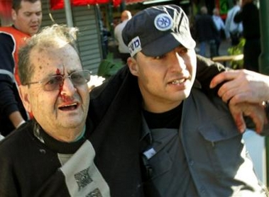 An Israel police officer helps a wounded man at the site of a suicide bombing in Tel Aviv,Israel, Thursday Jan. 19, 2006.