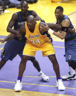 Shaquille O'Neal being defended by two Timberwolves players in the post.