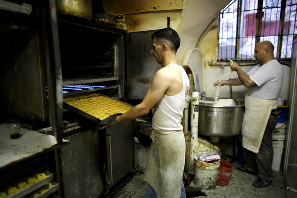 Workers prepare traditional cookies for Eid al-Fitr