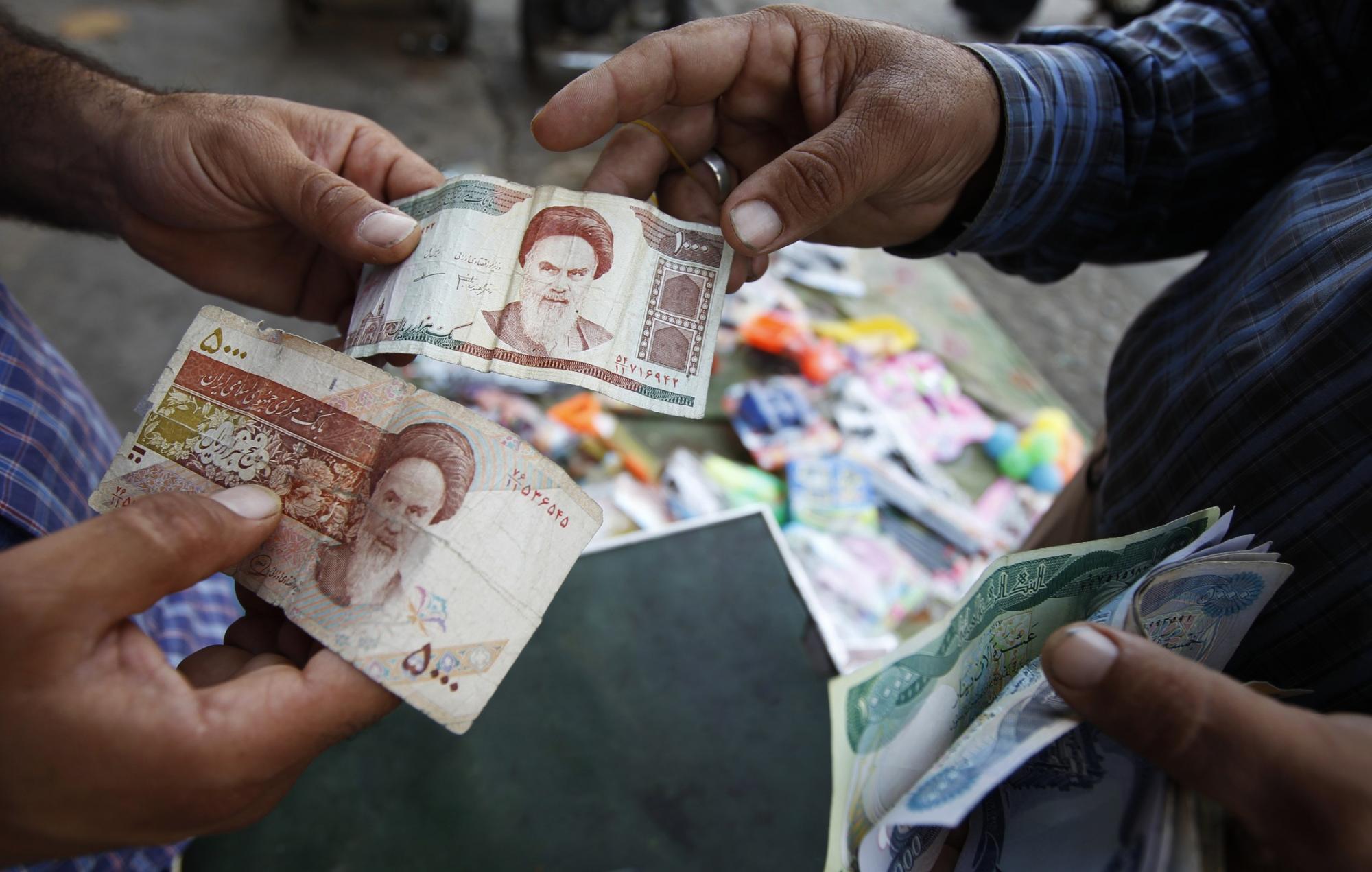 伊朗/一名消费者在兑换伊朗货币里亚尔。(资料图片)