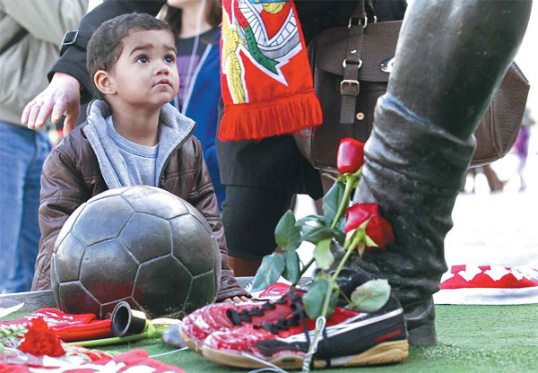 a young boy looks at a statue of late portuguese player