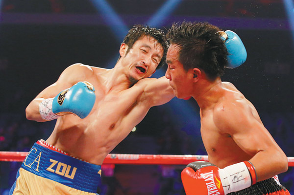 chinese boxer zou shiming left delivers a punch to yokthong kokietgym of thailand during their