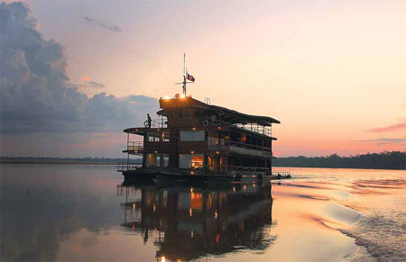 a cruise ship sails at sunset in the amazon jungle sailing ...