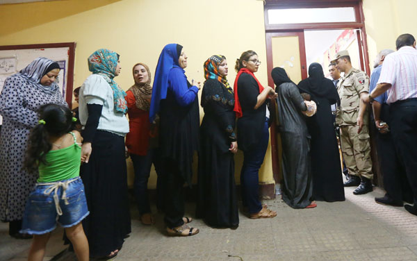 Egyptians wait to cast their vote inside a polling station for Farcical scenes over abbott s wild party