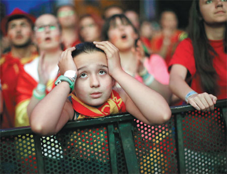 a spanish soccer fan holds her head as she watches on a ...