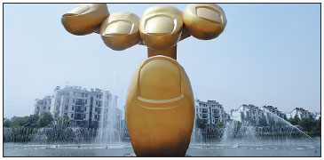 A Golden Finger Sculpture Stands In Front Of Yonglian