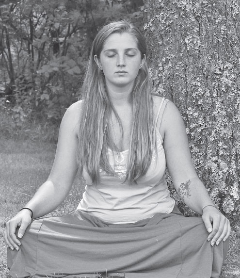 A Woman Sits In Meditation On The Grounds Of The Same