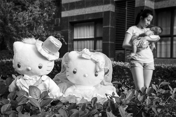 A Woman Holding A Child Passes Hello Kitty Dolls In A