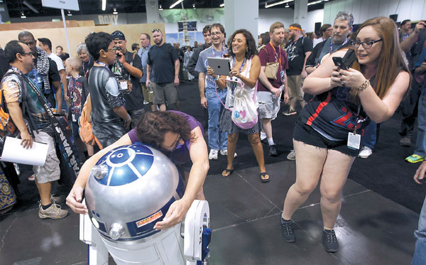 A Fan Hugs An R2 D2 Robot Character At The Star Wars