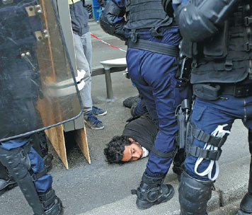 french riot police apprehend a man during clashes with protesters. Black Bedroom Furniture Sets. Home Design Ideas