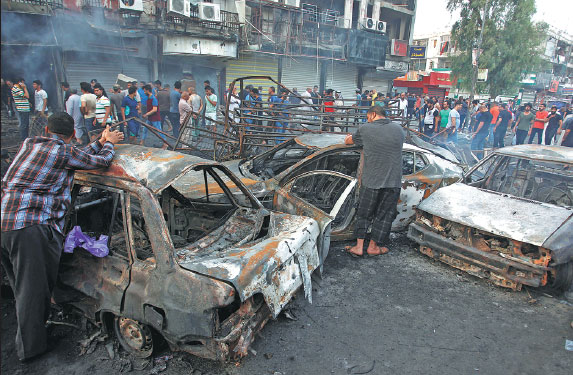 People Inspect The Site Of A Suicide Car Bombing In The