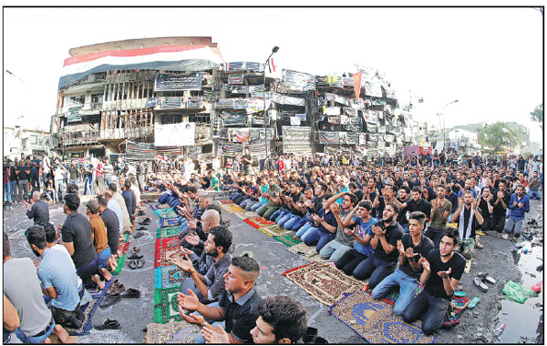 sunni and shiite muslims perform eid prayers at the site of sunday s suicide car bomb attack in. Black Bedroom Furniture Sets. Home Design Ideas