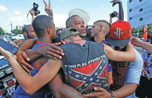 people including a man wearing a confederate flag hug