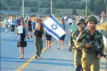 A Woman Carries The Flag Of Israel While Marching During A