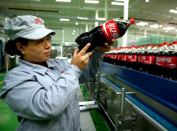 an employee of a cofco coca cola venture checks the ...